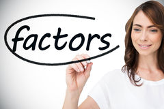 Businesswoman writing the word factors Stock Photo