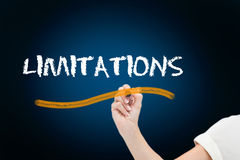 Businesswoman writing the word limitations Stock Photos