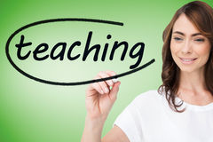Businesswoman writing the word teaching Stock Photo