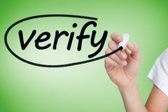 Businesswoman writing the word verify Stock Photo