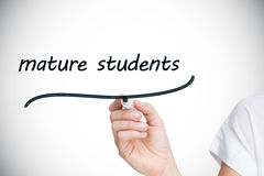 Businesswoman writing the words mature students Stock Photo
