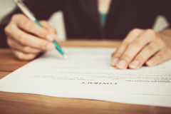 Businesswoman's hand with pen completing personal information Royalty Free Stock Image