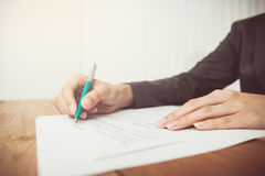 Businesswoman's hand with pen completing personal information Stock Photo