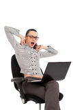 Businesswoman yawning in the office chair with laptop Stock Images