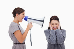 Businesswoman yelling at colleague with megaphone Royalty Free Stock Photo