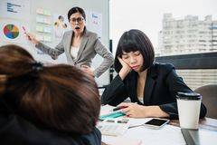 Businesswoman yelling at colleagues who doze off. The businesswoman is yelling at her colleagues who doze off in the meeting royalty free stock images