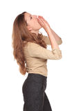 Businesswoman - yelling hand megaphone. Isolated studio shot of the side view of a Caucasian businesswoman yelling while using her hands as a megaphone Stock Photography