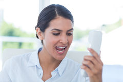 Businesswoman yelling at her phone Stock Photo