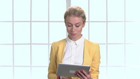 Businesswoman in yellow jacket with tablet. stock video