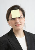 Businesswoman With Yellow Note. Attractive businesswoman with yellow sticky note on forehead Royalty Free Stock Photography