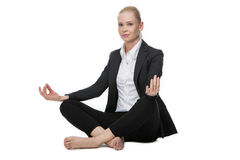 Businesswoman in yoga position. Blonde businesswoman seated on the floor doing a yoga position Stock Photo