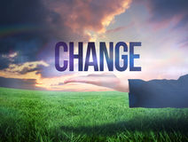 Businesswomans hand presenting the word change. Against green field under orange sky Royalty Free Stock Image