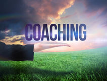 Businesswomans hand presenting the word coaching. Against green field under orange sky Royalty Free Stock Photo