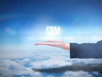 Businesswomans hand presenting the word crm. Against blue sky over clouds at high altitude Royalty Free Stock Image