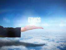 Businesswomans hand presenting the word ethics. Against blue sky over clouds at high altitude Stock Images