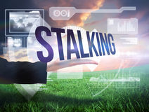 Businesswomans hand presenting the word stalking. Against green field under orange sky Stock Image