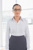 Businesswomanstanding de sorriso em seus vidros vestindo do escritório Foto de Stock