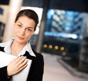 Businesswomen. Young businesswomen is posing with laptop in front of an officebuilding Royalty Free Stock Photography