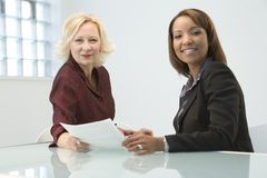 Businesswomen. Two businesswomen with contract paper royalty free stock photos