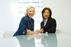 Businesswomen. Two happy middle-aged businesswomen in an office stock photo