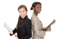 Businesswomen. Two attractive young business women with clipboards on white background Stock Photos