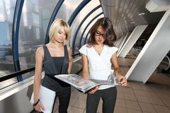 Businesswomen. Two businesswomen looking into folder in futuristic interior royalty free stock photos