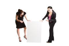 Businesswomen with billboard. An isolated shot of two businesswomen pointing at a blank billboard royalty free stock photo