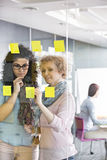 Businesswomen brainstorming with sticky notes in office royalty free stock photos