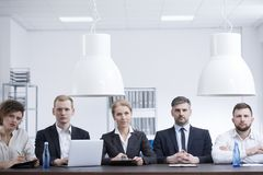 Businesswomen and businessmen during meeting. Businesswomen and businessmen in black suits sitting at a desk in a corporate office during a meeting Stock Photos