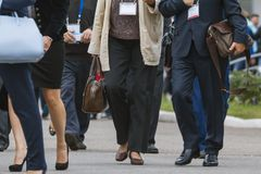 Businesswomen and businessmen walking along street at conference or exhibition stock photos