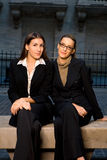 Businesswomen in City Setting. Two Businesswomen Sitting on Bench in City Setting Stock Images