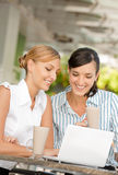 Businesswomen with Coffee. Two attractive businesswomen chatting over coffee Royalty Free Stock Images