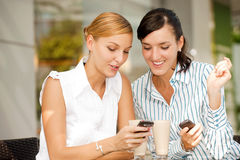 Businesswomen with Coffee. Two attractive businesswomen chatting over coffee Stock Images
