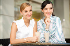 Businesswomen with Coffee. Two attractive businesswomen chatting over coffee Royalty Free Stock Photography
