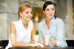 Businesswomen with Coffee. Two attractive businesswomen chatting over coffee Royalty Free Stock Image