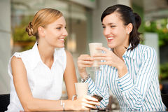 Businesswomen with Coffee. Two attractive businesswomen chatting over coffee Royalty Free Stock Photo