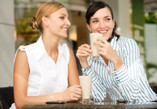 Businesswomen with Coffee. Two attractive businesswomen chatting over coffee Stock Photography