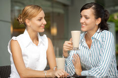 Businesswomen with Coffee. Two attractive businesswomen chatting over coffee Stock Photos