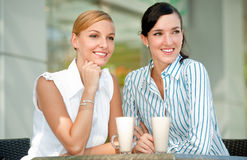 Businesswomen with Coffee. Two attractive businesswomen chatting over coffee Royalty Free Stock Photos
