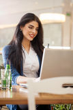 Businesswomen with coffee working at laptop in cafe. Young woman in restaurant on coffee break working on lap top Stock Images