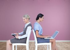 Businesswomen collaborating working back to back on chairs Stock Photos