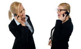 Businesswomen communicating via mobile phones. Isolated on white background Stock Photography