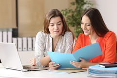 Businesswomen consulting a report together. Two businesswomen consulting a report together on a desk at office royalty free stock photo