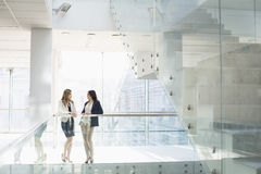 Businesswomen conversing against railing in office Royalty Free Stock Photo