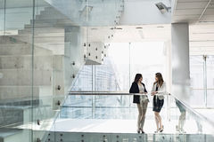 Businesswomen conversing against railing in office stock photography