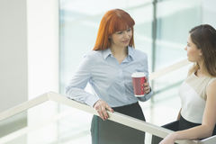 Businesswomen conversing while having coffee in office Stock Photography
