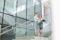 Businesswomen conversing while having coffee on steps in office Royalty Free Stock Photo