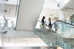 Businesswomen conversing while moving down steps in office stock image