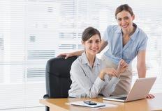 Businesswomen at desk smiling at camera Royalty Free Stock Image