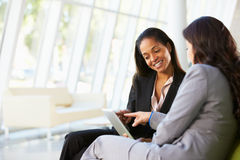 Businesswomen With Digital Tablet Sitting In Modern Office Royalty Free Stock Photo